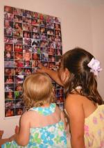 Anna and Malia look at pictures on their life poster.